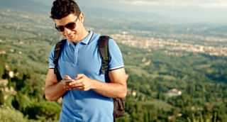 Nature and Technology Concept Young Man Smart Phone Outdoors Backpacking