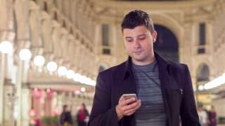 Handsome Young Businessman Walking Through Landmark Shopping Center In Europe Using His Smartphone Work And Travel Concept