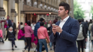 Happy Young Businessman Using His Phone While On Vacation Traveling To Europe Remote Work Internet Connection 3G 4G Wi-Fi Reception Concept