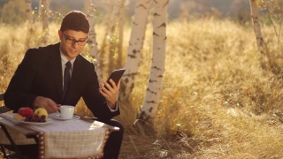 Young businessman using tablet pc having breakfast