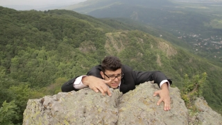 Business Risk for Success Businessman Hanging from Cliff