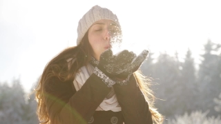 Attractive Young Woman Blowing Snow Flakes At Camera Sun Flare