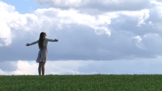 Woman with outstretched hands on a spring field