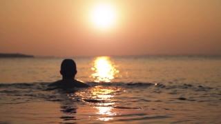 Man Swimming at Sunset Background HD