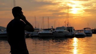 Young Man Talking on Phone at Sunset Sea Boats HD