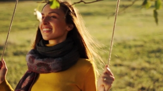 Happy Young Woman Enjoying Swing in Nature