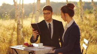 Business People having breakfast using tablet