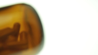 Panning over Spilled Pill Bottle White Background