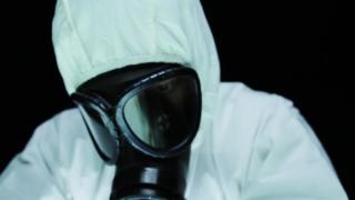 Man Gas Mask Looking at Radioactive Chemical Beaker Danger