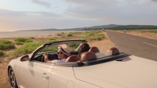 Cute Young Couple Man And Woman Arriving At Beach In Convertible Car Parking At Sand Enjoying Mediterranean Coast Vacation Beautiful Sunset Colors Sunshine Holiday