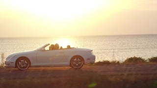 Young Couple Enjoying Driving A Cabriolet Car On Summer Sea Holiday At Beautiful Sunset Beach Vacation Carefree Happiness Concept