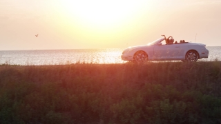 Young Fun Couple Driving Convertible At Sunset At Sea Front Beach Woman Waiving Hands Dancing Joy Adventure Flyover Drone Shot