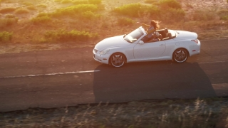 Young Couple Driving Convertible Car At Sunset By The Sea Front Beach Aerial Fly By Summer Adventure Sunshine Happiness