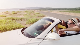 Romantic Couple Arriving At Beach On Summer Vacation In Cabriolet Convertible Car Summer Joy Steadycam Shot