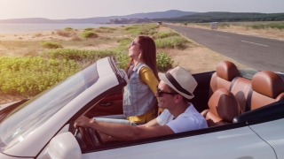 Joyful Happy Young Romantic Couple Arriving At Beach Front Vacation Ocean Sunset Convertible Car Cabriolet Travel Trip Exotic Location Concept