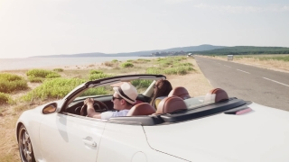 Slow Motion Of Convertible Car Arriving At Beach Young Romantic Couple Exiting Enjoying Honeymoon Vacation Trip Beautiful Seaside Beach Sunset