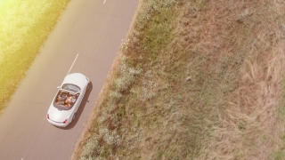 Aerial Flight Over Convertible Car Driving Down Countryside Road At Sunset Travel Adventure Concept