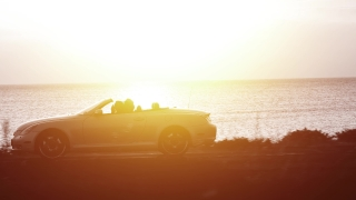 Aerial Drone Flight Tracking Convertible Car Silhouette By Sea Sunset Young Couple Driving Toward Vacation Destination Happy Joy Relaxation