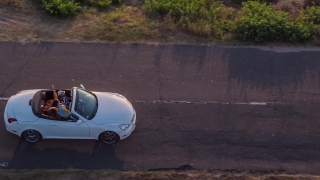 Aerial Shot Of A Couple In A Cabriolet Driving By The Seaside Woman Taking Pictures Tourists Travel Destination Concept