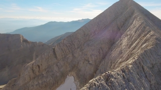 Aerial View Of Young Man Climbing On Top Of Mountain Sunny Hiking Edge Drone Rock Adventure Travel Extreme Sport Beautiful Exploration Landscape Freedom