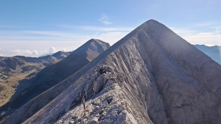 Young Man Relaxing On Edge Of Mountain Cliff Extreme Sport Climbing Hiking Aerial Drone Landscape Adventure Tourism Top Peak Timelapse Sky Scenery