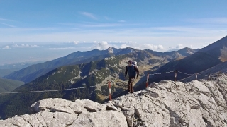 Man With Backpack Hiking On Edge Of Mountain Cliff Extreme Sport Adventure Landscape Healthy Lifestyle Walking 4K Rock Nature Peak Scenic