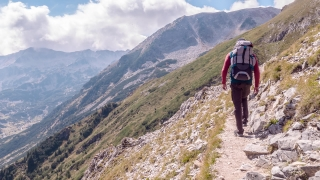 Young Man With Backpack Hiking On Mountain Trail Adventure Extreme Sport Leisure Lifestyle Freedom Scenic Travel Victory