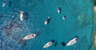 Aerial Drone Shot Passing Over Tourist Boats and Yachts at Rocky Tropical Ocean Island Shore Famous Zante Island Tourist Attraction Summer Travel Concept On Hot Summer Day