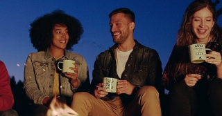 Attractive Multiracial Group Of Young Friends Sitting And Smiling Around Forest Camp Fire In The Evening Laughing And Holding Cups Hiking Lifestyle Teen Life Adventure Concept Slow Motion Shot On Red