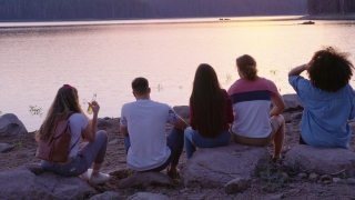 Diverse Group Of Attractive Young People Sitting And Laughing On Lake Shore Talking Friendship And Happiness In The Wild Romantic Getaway Concept Slow Motion Shot On Red Epic W 8k