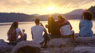 Attractive Multiracial Group Of Young Friends Sitting On Lake Shore Socializing Looking at Beautiful Sunet Close Friendship And Tourism Travel Party Concept Slow Motion Shot On Red Epic W 8k