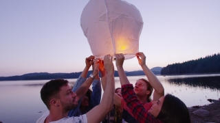 Diverse Group Of Young Men And Women Holding A Sky Lantern Smiling And Releasing it Camping Youth Togetherness Romantic Getaway Concept Slow Motion Shot On Red Epic W 8k