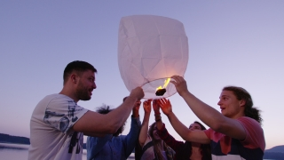Happy Young Group Of Friends Releasing Sky Lantern On Lake Shore at Dusk Smiling Close Friendship And Tourism Slow Motion Shot On Red Epic W 8k
