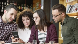 Trendy Young Group Of Men And Women Looking At A Smartphone At A Coffee Bar Smiling And Laughing Friendship Technology Phone Apps Startup Concept Slow Motion Shot On Red Epic 8K