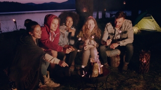 Attractive Multiracial Group Of Young Friends Sitting Around Bonfire At Dusk In Forest Laughing And Holding Marshmallows Hiking Lifestyle Happiness In Nature Concept Slow Motion Shot On Red Epic W 8k