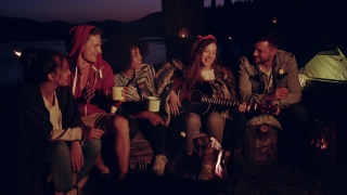 Happy Young Group Of Campers Sitting Around Bonfire In Forest Singing Along To Guitar Drinking And Laughing Music As Lifestyle Musical Leisure Concept Slow Motion Shot On Red Epic W 8k
