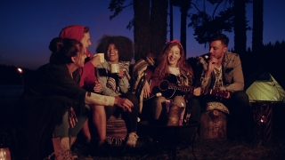 Diverse Group Of Attractive Young People Playing Guitar And Singing Around Forest Camp Fire Drinking And Clapping Close Friendship Tourism Romantic Musical Getaway Concept Slow Motion Shot On Red Epic