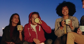 Diverse Group Of Young Men And Women Sitting And Smiling Around Forest Camp Fire In The Evening Drinking Tea And Laughing Hiking Lifestyle Teen Life Adventure Concept Slow Motion Shot On Red Epic W 8k