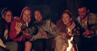 Attractive Multiracial Group Of Young Friends Around Burning Camping Bonfire In The Woods Taking a Selfie And Smiling Nature Tourism Technology Concept Slow Motion Shot On Red Epic W 8k