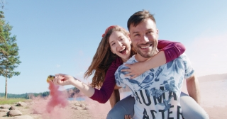 Happy Couple Man Carrying Woman On His Back On Beach Lake Shore Passing Through Clouds Of Smoke Sunny Day Summer Romantic Vacation Young Love Concept Slow Motion Shot On Red Epic W 8k