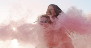 Attractive Young Happy Couple Man And Woman Spinning And Laughing On Piggyback At Lake Shore Passing Through Clouds Of Smoke Romantic Getaway Marriage And Love Concept Slow Motion Shot On Red Epic W 8