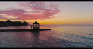 Aerial Drone Shot Over Romantic Couple Silhouettes Walking on a Pier at Sunset Tropical Paradise Panorama Traveling To New Destinations Caribbean Vacation Holiday Concept At Golden Hour Dusk Slow Moti