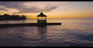 Aerial Drone Shot Over Beautiful Caribbean Ocean Pier at Sunset Jamiacan Nature Landscape Traveling To New Destinations Summer Vacation Concept At Golden Hour Dusk Slow Motion 4k
