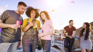 Diverse Young Party People On Rooftop Socializing Looking at Smartphone Friendship Happiness Youth Party People Social Networking Concept At Sunset Shot on Red Epic W 8K Slow Motion