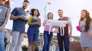 Young People At Celebration Rooftop Party Flying Uav Quadcopter Smiling Happy Party Trick Friendship And Technology Concept During Golden Hour Shot on Red Epic W 8K Slow Motion