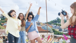 Group Of Diverse Teen Girls On Rooftop Posing As Young Female Photographer Takes Pictures Of Them Fashion Photography Festive Photoshoot Party Carefree Friendship Cheerful Artsy Lifestyle Concept At B