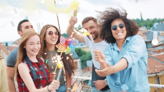 Festive Group Of Beautiful Diverse Young Friends Waving Sparkler Fire And Smoke Torch In Hands Enjoying Fireworks And Confetti Happy Party Festive Time Happy Event Concept During Beautiful Urban Sunse
