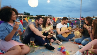 Group Of Diverse Teen Friends On Rooftop Sitting Down And Moving In Rhythm To Man Playing Guitar Happy Drinking And Eating Pizza Outdoors Festive Music Pizza Party Young Carefree Friendship Concept At