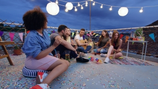 Young Friendly People At Celebration Rooftop Party As Man Plays Guitar And Friends Dance In Rhythm Happy Drinking And Eating Pizza Outdoors Festive Music Pizza Party Young Carefree Friendship Concept