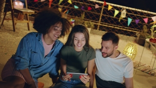 Diverse Young Party Friends On Rooftop Looking At A Tablet Smiling And Sharing Funny Internet Videos Looking At A Project Together Teamwork Fun Time With Technology At Party 3g 4g 5g Future Communicat